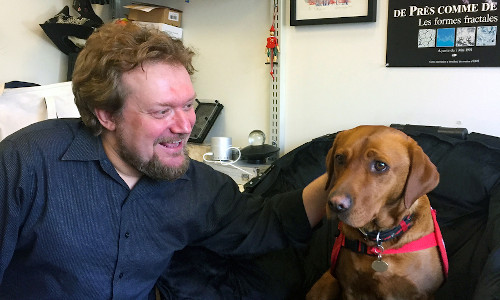 Andreas Mershin visits with one of the disease-sniffing dogs.